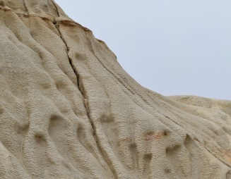 This ancient dune, pressed into rock, is now crumbling away.